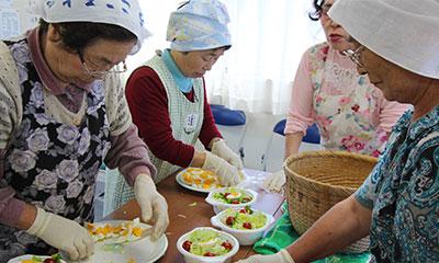 三角巾をかぶり、華やかなエプロンをかけたおばさんたちが、サラダをつくっています。