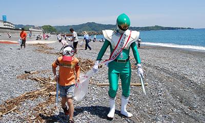 緑色の明社レンジャーと少年が砂浜でゴミ拾い