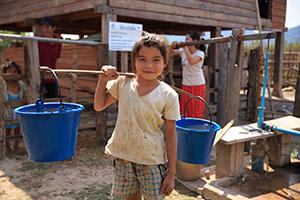 ラオスで水汲みをする少女